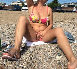 Old lady on the beach removes panty to show shaved pussy