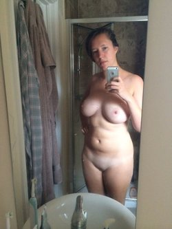 Brunette MILF with a natural body is doing self shot in front of the bathroom mirror