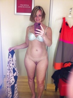 Sexy woman without panties takes a nude selfie in the changing room