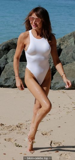 Lizzie Cundy pokies in white swimsuit on the beach